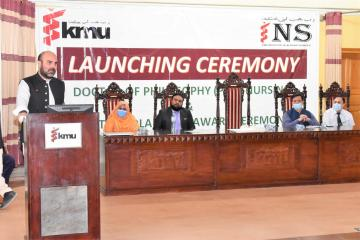 02.Minister of Health Taimur Salim Jhagra talking to PhD Launching Ceremony VC KMU Prof Dr Zia ul Haq and others are also sitting on stage1604146039.JPG